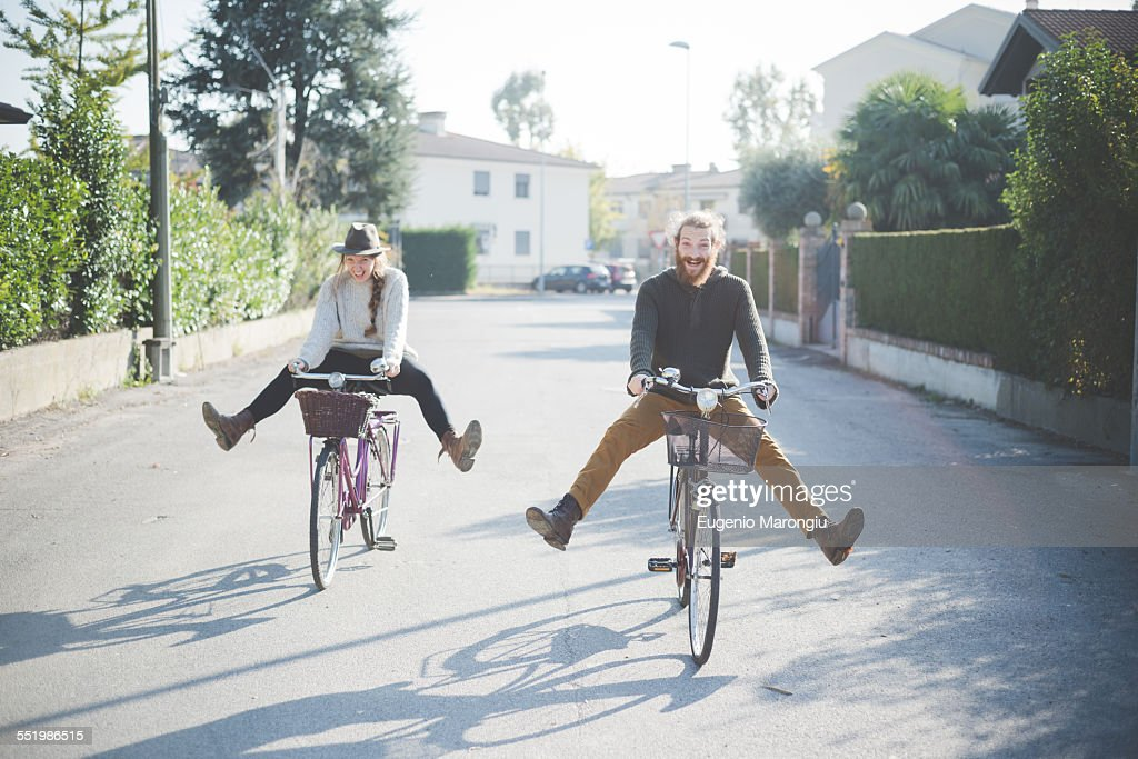 Young couple cycling with legs out