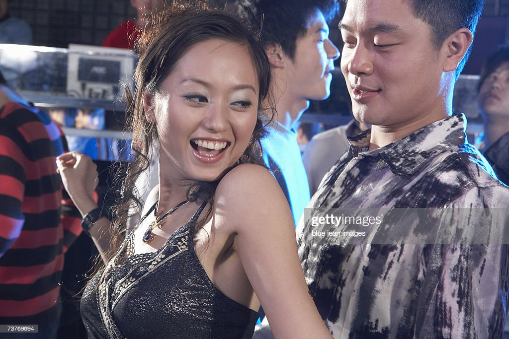 A young couple dance in a nightclub : Stock Photo