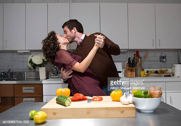 Young couple dancing and kissing in kitchen while cooking
