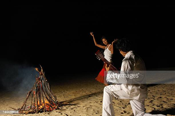 A young couple dancing by a bonfire