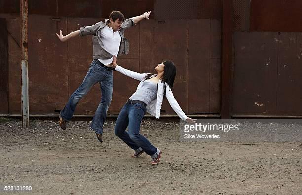 Young couple dancing in courtyard
