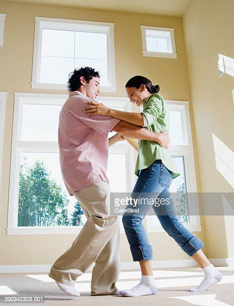 Young couple dancing in empty room, side view (blurred motion)
