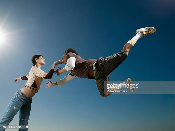 Young couple dancing, low angle view