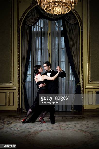 Young couple dancing the tango in an elegant room