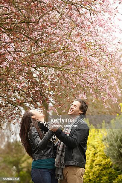 Young couple dancing under blossom in park