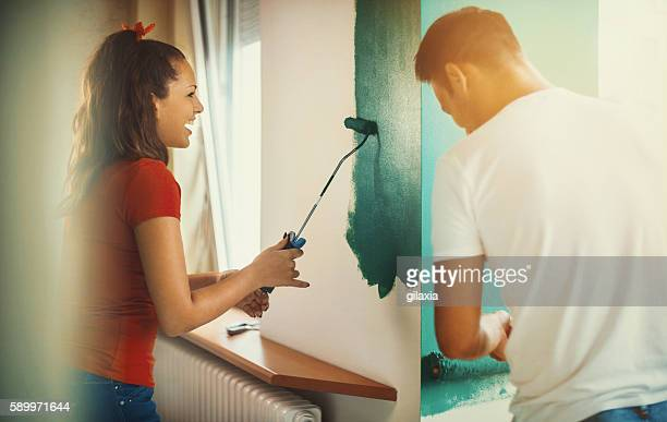 Young couple decorating apartment.