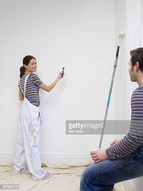 Young couple decorating room