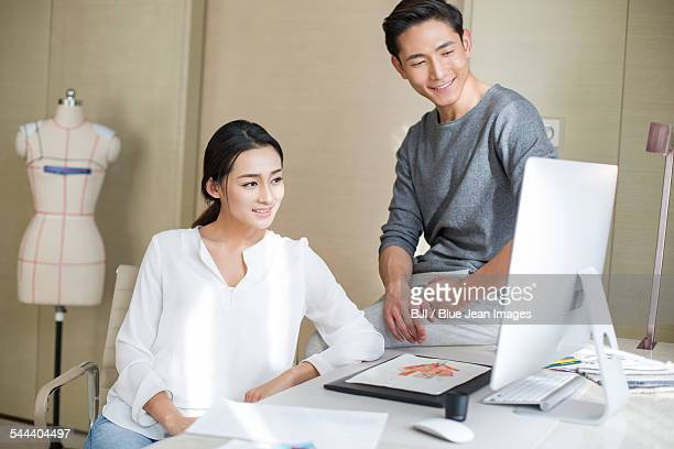 Young couple designing clothing together