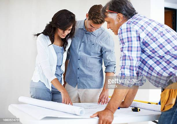 Young couple discussing house plan with architect