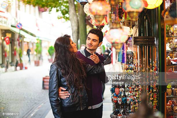 Young Couple Discussing Shopping Items in a Street Market