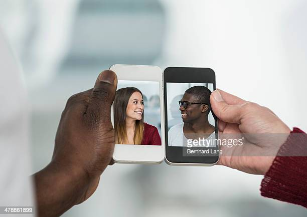 Young couple displayed on two smartphones
