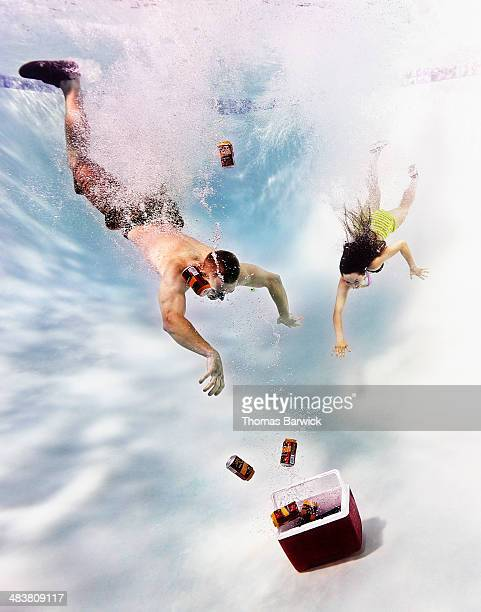 Young couple diving underwater after cooler