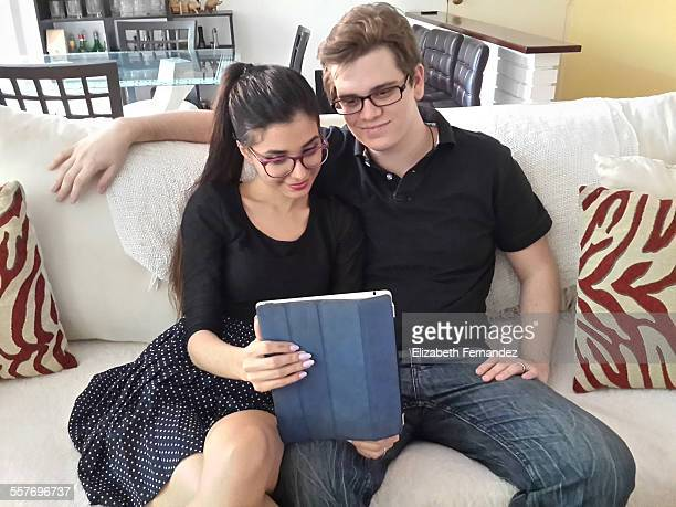 Young couple doing a Face Time with his family on Ipad tablet