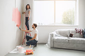 Young man and woman doing apartment repair together paint walls
