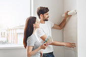 Young man and woman doing apartment repair together wallpapering