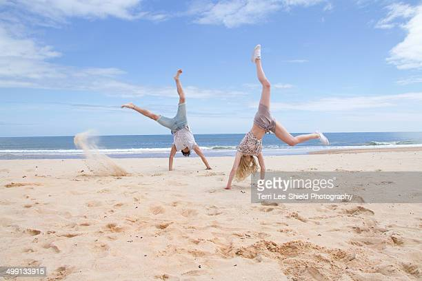 Young couple doing handstands on beach