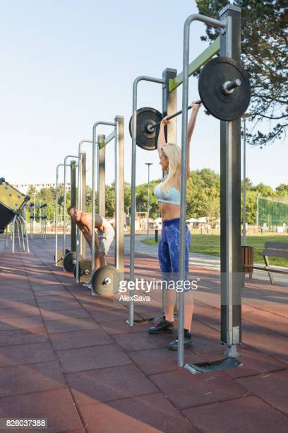 Young couple doing hard calisthenics exercises outdoor in the park