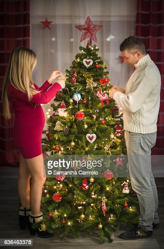 Young Couple doing the Christmas Tree. Woman Pregnant. Family. Pregnancy. : ストックフォト