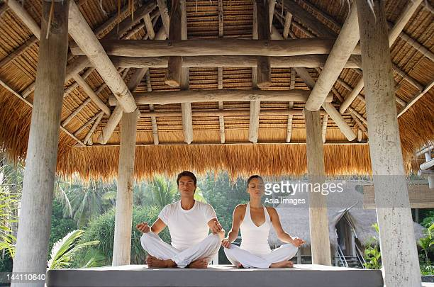 young couple doing yoga in outdoor sala