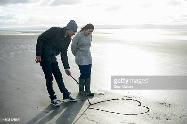 Young couple drawing heart in sand, Brean Sands, Somerset, England