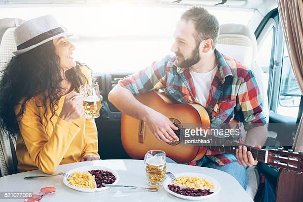 Junges Paar trinken Bier und Spielen Sie auf Gitarre in Wohnwagen