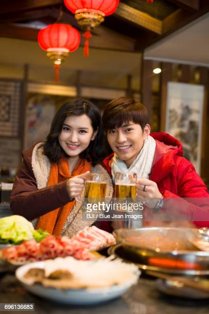 Young couple drinking beer in hotpot restaurant