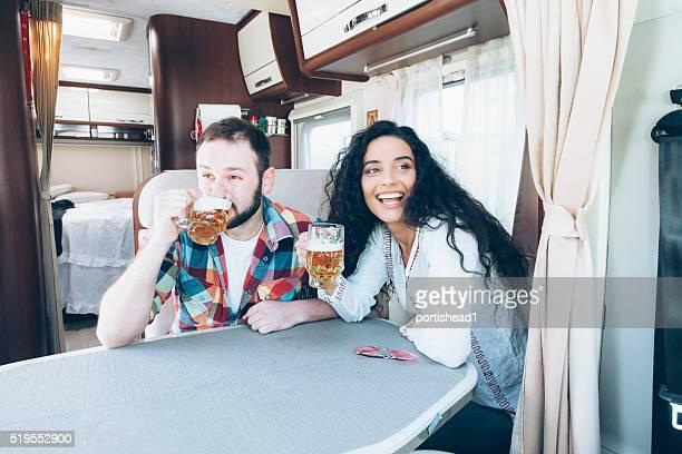 Junges Paar trinken Bier im Inneren des Wohnwagen