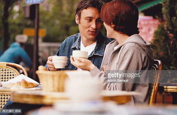 Young couple drinking coffee at outdoor cafe, Paris, France