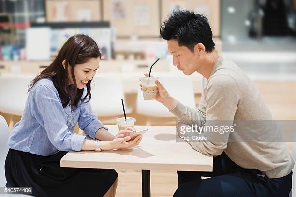 若いカップルに飲むコーヒーカフェ」。