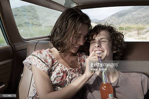 Junges Paar trinken Mineralwasser im Auto