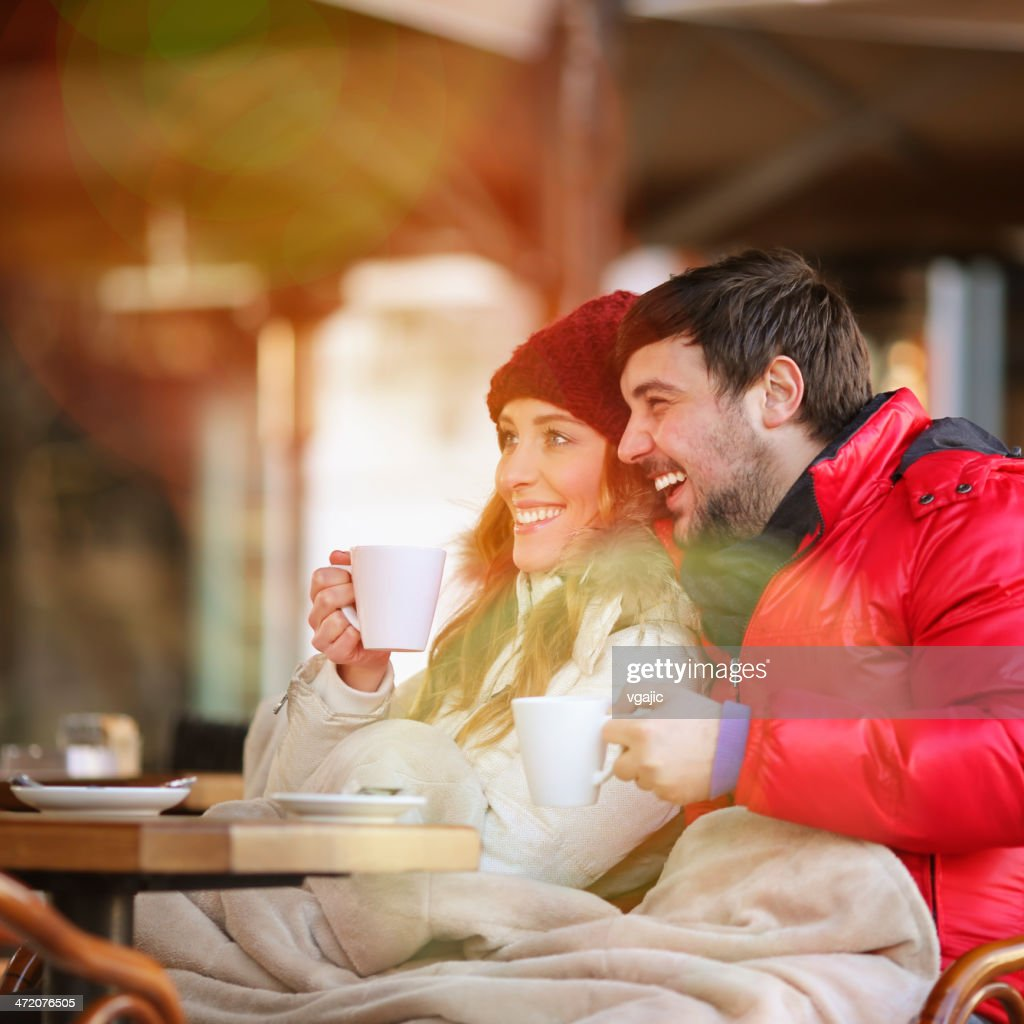 Young couple drinking tea in winter outdoors.