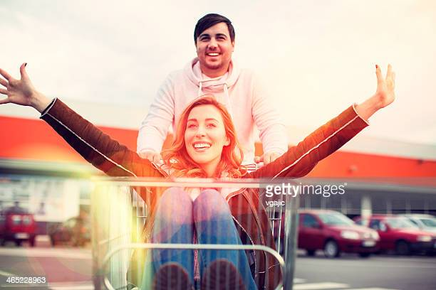 Young Couple Drive Shopping Cart Outdoors.
