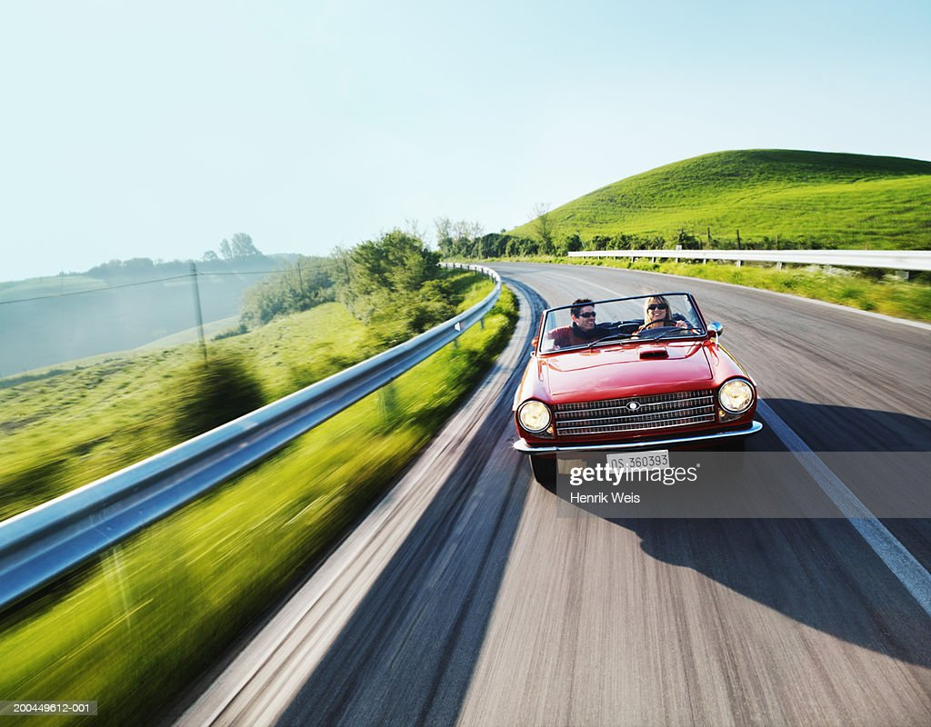 Young couple driving convertible car in countryside (blurred motion) : Stock Photo