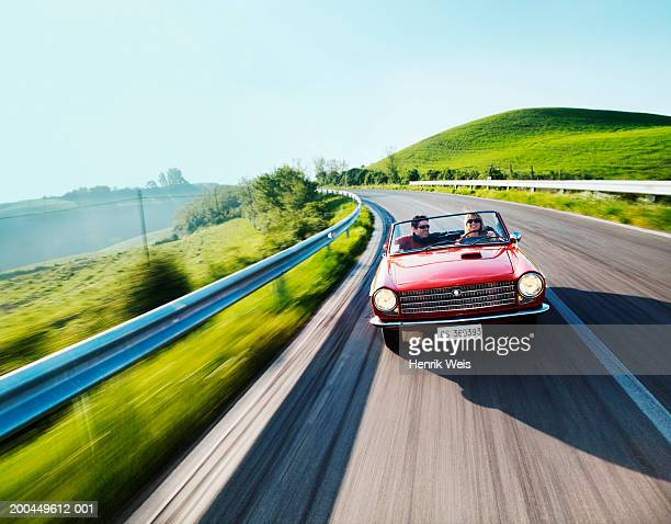 Young couple driving convertible car in countryside (blurred motion)