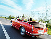 Young couple driving convertible car in countryside, rear view