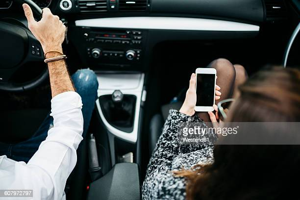 Young couple driving in a car, co driver using smart phone