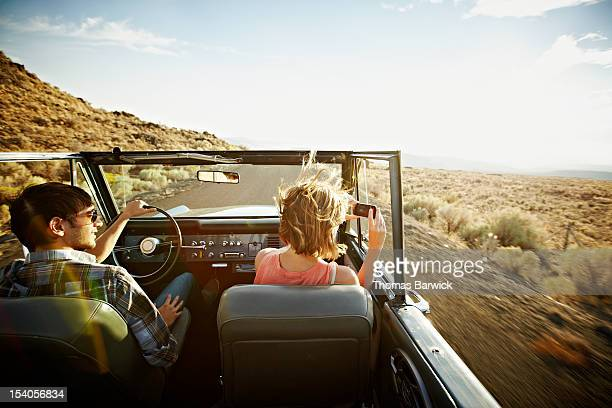 Young couple driving woman taking photo
