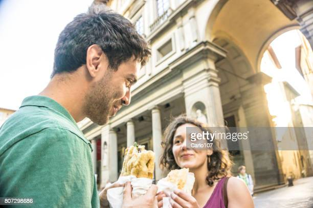 Young couple eating a sandwich