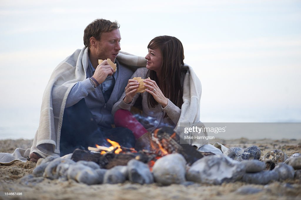Young couple eating at beach party : Stock Photo