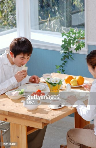 A young couple eating breakfast : Stock Photo