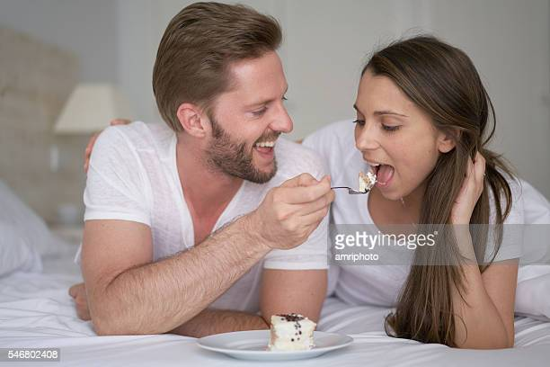 young couple eating cake in bed
