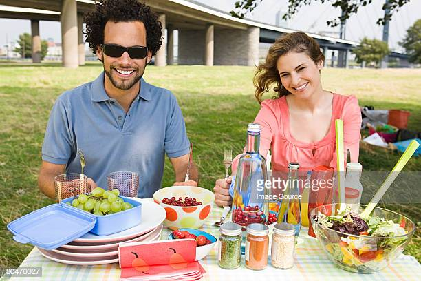 Young couple eating lunch in a field