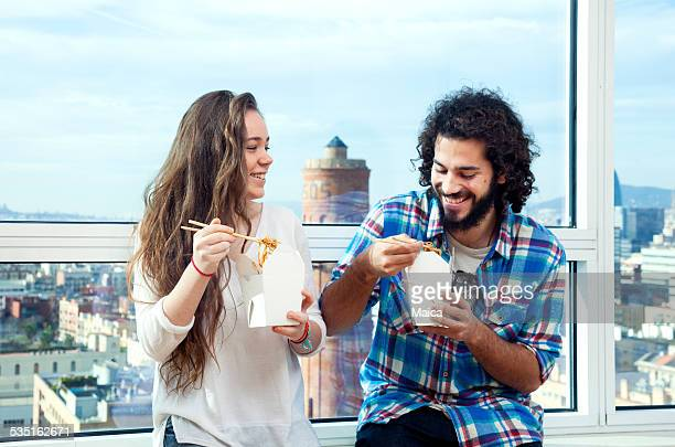 Young couple eating take away food at home