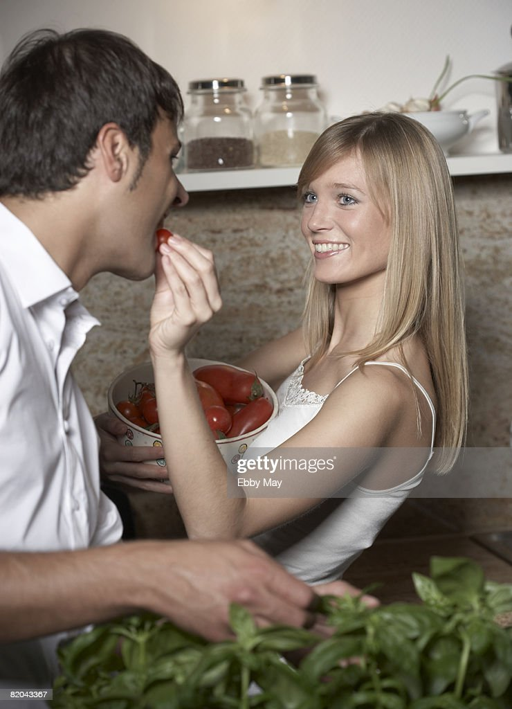 Young couple eating tomatoes : Stock Photo