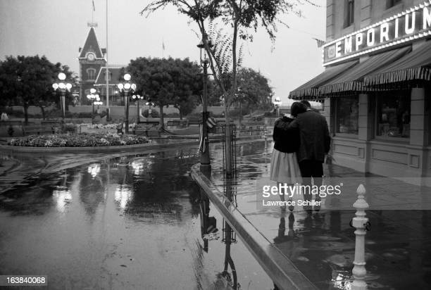 A young couple embrace as they walk together along a rainy street during an adultsonly night at the Disneyland theme park Anaheim California early...