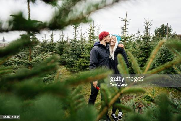 Young Couple Embrace While Walking Through Pine Forest