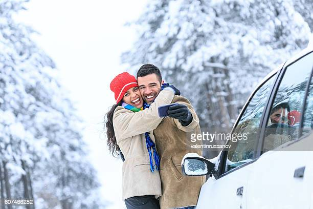 Young couple embracing and making selfie on snow footpath