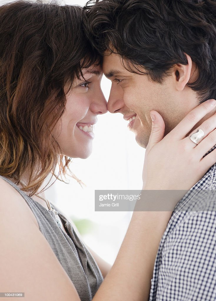 Young couple embracing and smiling at one another : Stock Photo