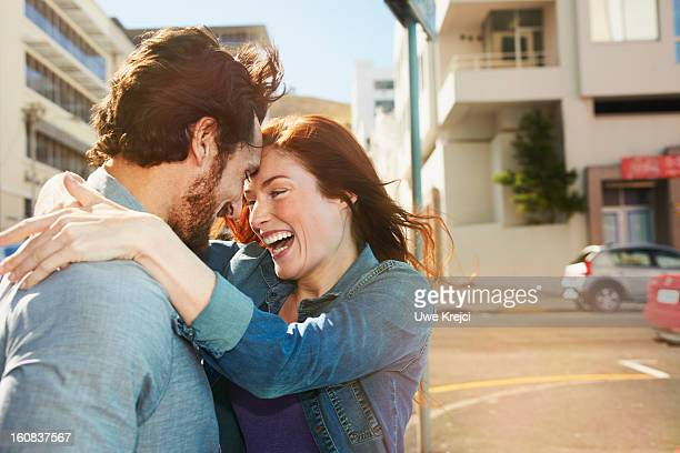 Young couple embracing and smiling in the city