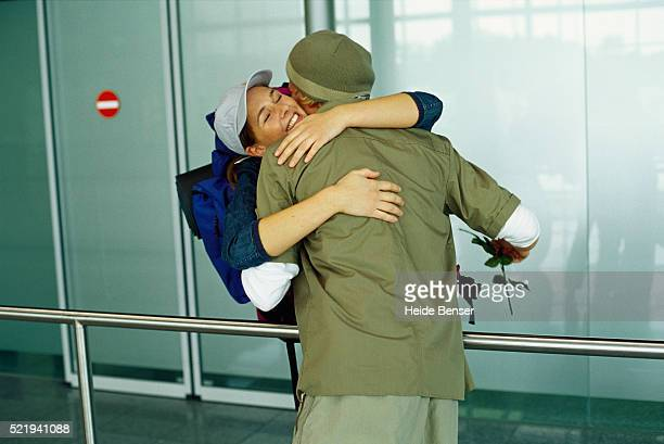 Young couple embracing at airport